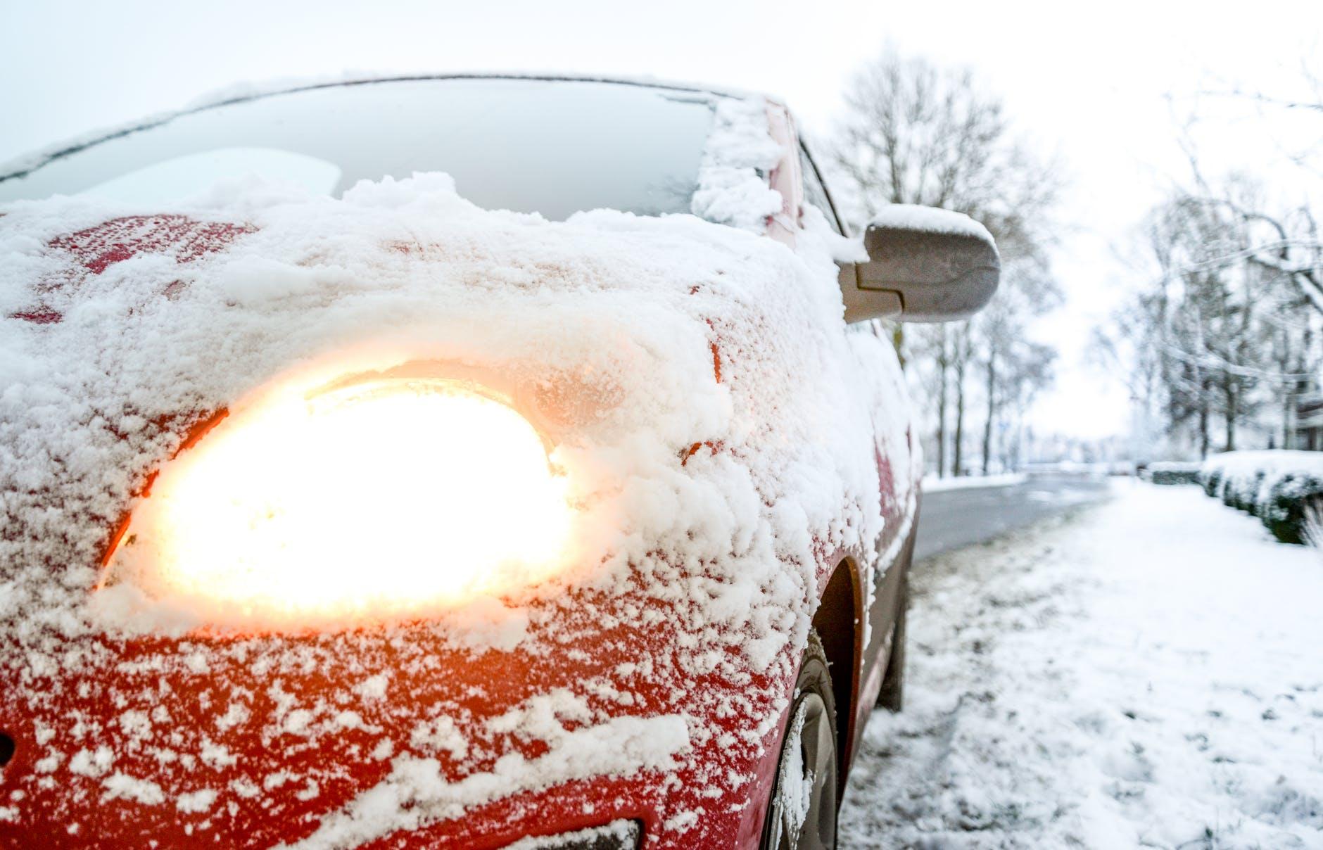 snow covered red sedan